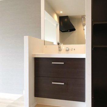 キッチンの隣に洗面台。大きな鏡が使いやすそう!(※写真は5階の反転間取り別部屋、清掃前のものです)