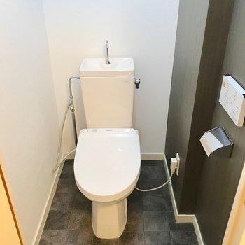 トイレはウォシュレット付き。グレーの壁紙で落ち着く印象。