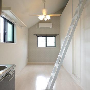 洋室は縦長の空間。ライトの下にテーブルと、窓際にシングルベッドを。