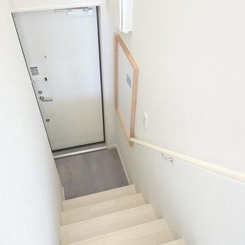 階段を降りた先に玄関。右にマグネットボード、左に靴箱があります。