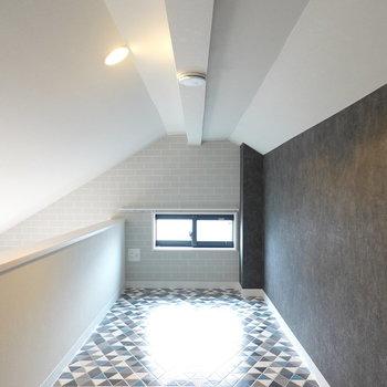 ロフトは三角形のパターン柄の床と黒のアクセントクロスでスタイリッシュに。