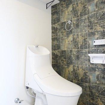 トイレのフォルムが未来感ある。石調のアクセントクロスが遊び心。
