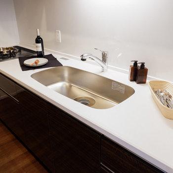 コンロは三口のシステムキッチン。お料理も洗い物も手分けしやすいです。※写真は29階同間取り別部屋のものです