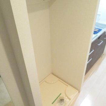キッチンの隣に洗濯機置き場が。その上には棚もあります