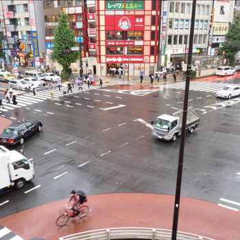 窓からは交差点を行き交う車や人が見えます