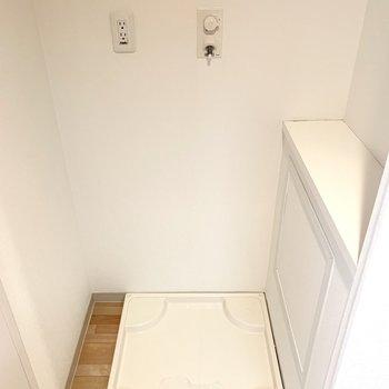 扉付きの洗濯機置場。棚もあります。