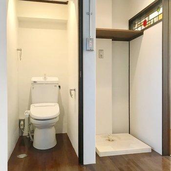 扉の中身はトイレ。ウォシュレット付きです。洗濯機上の棚も嬉しい。