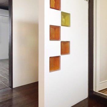 水回りと居室を分ける白い壁。POPな色のガラスがレトロ。