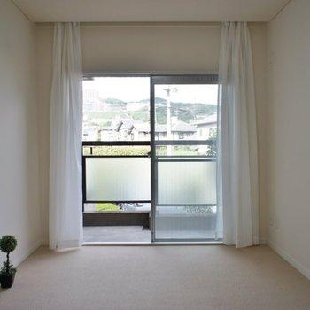 バルコニー付きの洋室、床は絨毯