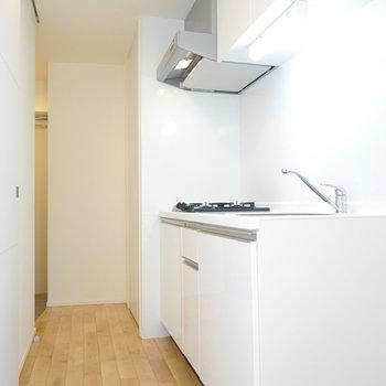 キッチン右手に冷蔵庫を。左は洗面所への入り口で、奥が玄関。