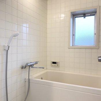 洗面化粧台の奥は、窓付の浴室。追焚き機能付です。※写真はクリーニング前