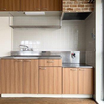 キッチンはガスコンロ持込タイプ。グレーのタイルが素敵。左側は冷蔵庫スペース。
