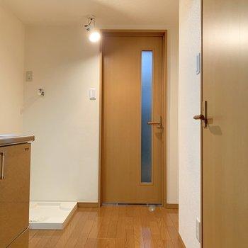 玄関側からみた洋室です。左側にキッチン、その隣には洗濯機置き場がありますね。※写真は1階の同間取り別部屋のものです