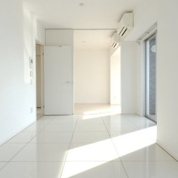 真っ白の空間のリビングです。奥が寝室(※写真は8階の反転間取り別部屋のものです)