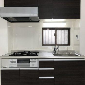 キッチンはダークブラウンでシック。※写真は2階の同間取り別部屋のものです