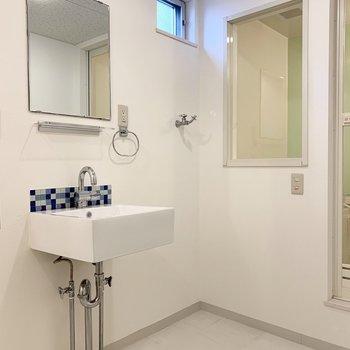 入って左手にタイルのかわいい洗面台と洗濯機置場。パンはないタイプ。