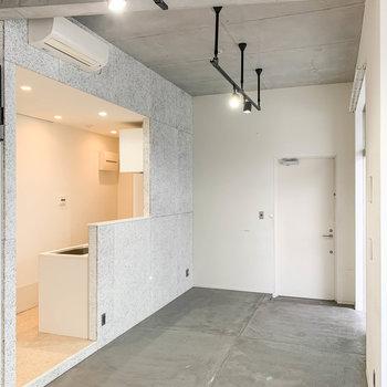 【LDK】床は土間、天井はコンクリート打ちっ放しです。キッチン側に玄関があります。