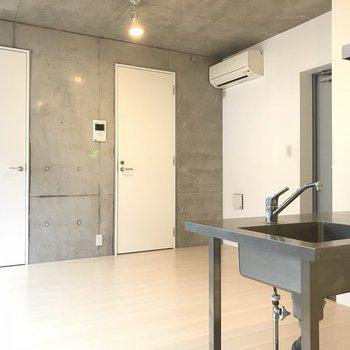 コンクリート打ちっぱなしの壁。ドアは純白※写真は2階の同間取り別部屋のものです