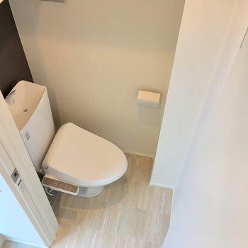 シックな印象の個室トイレ。ストックは上部のラックに。