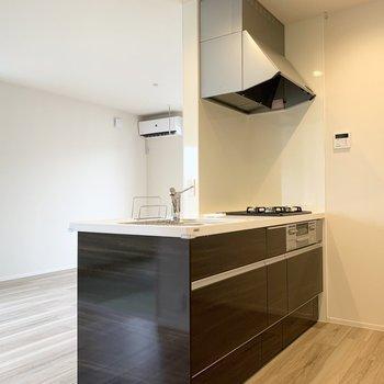 スタイリッシュなダークブラウンの対面キッチン。(※写真は2階の同間取り別部屋のものです)