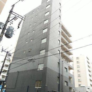 大通りに面している黒の大きなマンション。