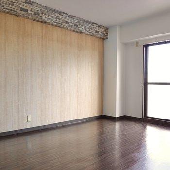 【リビング】木目のアクセントクロスとダークウッドの床材が落ち着いた雰囲気を醸し出しています。