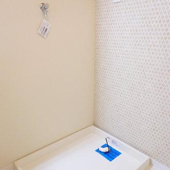 洗濯機置場は洗面台横。タイル風の壁紙がカワイイ。