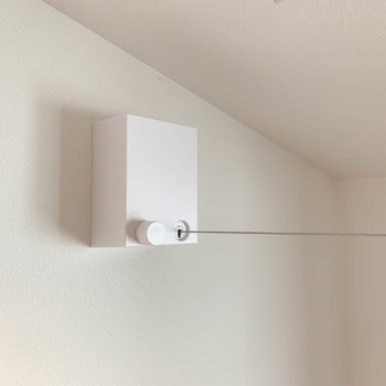 ベッドルームの窓辺沿いに、室内干しのワイヤーがあります。