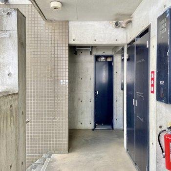 3階の共用廊下も打ちっぱなしにネイビーのドアがよく映える。