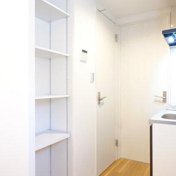 キッチン後ろの高さが変えられる棚にはレンジや炊飯器などを置いて。左がトイレ、右が脱衣所のドア。