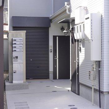 建物の左手奥がお部屋の入り口。玄関の隣のシャッターを開けると…?