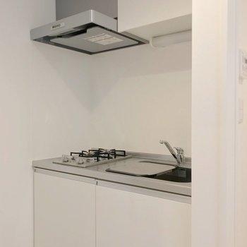 白いキッチンは清潔感たっぷり。向かいに冷蔵庫置場があります。