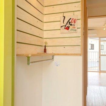 木製のボードがお出迎え。黄緑のドアとの組み合わせが素敵。