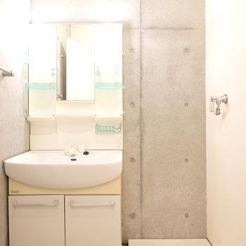 脱衣所はコンクリ壁で落ち着いた雰囲気。洗濯機置き場がここにあるのも嬉しいポイント。