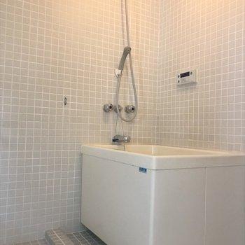 コンパクトな浴槽の前に洗濯機 置き場があります。