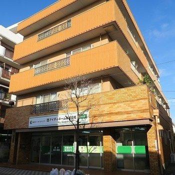 商店街沿いに立つ4階建てマンション※写真は前回募集時のものです