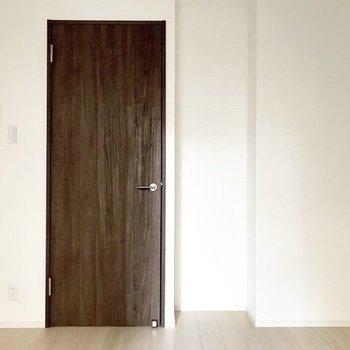 ドア横のくぼみには収納棚を置くのもいいですね。