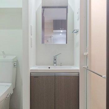 シックな雰囲気の洗面台。横にタオル掛けがあるのがGOOD。※写真は2階の同間取り別部屋のものです