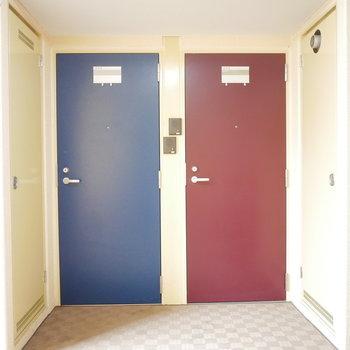 共用廊下から見ると玄関扉はシックなレッド