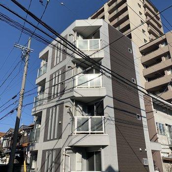 角地に立つ4階建てのアパートです。