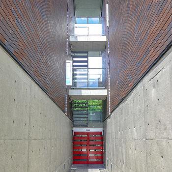 【共用部】コンクリートとレンガの双璧に、赤いドア。建築的に美しい。