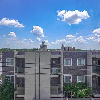 【バルコニー】正面の眺望は道路の向かい側の建物と、広くて青い空。