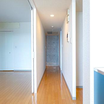 【廊下】右手に脱衣所のドア、左奥に玄関。