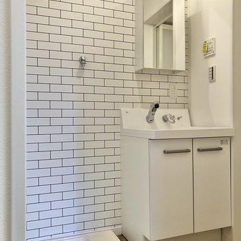 左のドアの先には、清潔感のある洗面台と洗濯機置き場。※写真は2階の同間取り別部屋のものです