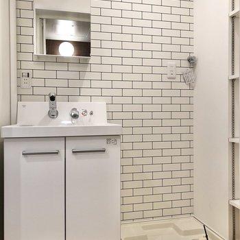 清潔感のある洗面台と洗濯機置き場。※写真は2階の同間取り別部屋のものです