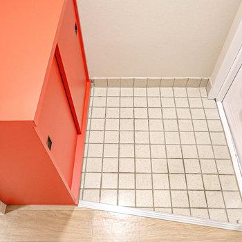 白いタイルの土間と真っ赤な靴箱が対照的。