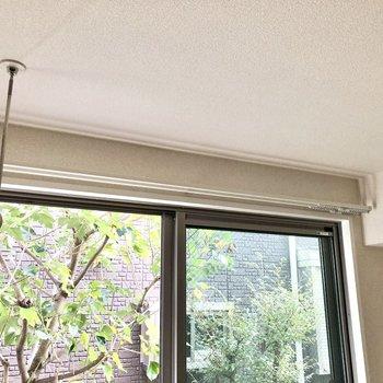 窓の近くに室内物干し竿掛けがあります。