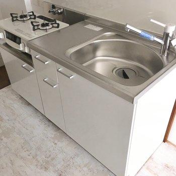キッチンは真っ白の2口コンロがついています。作業スペースもあるのでお料理もさくっとね。