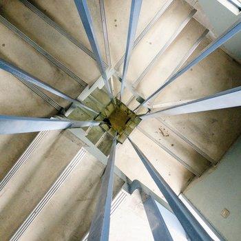 共用部には青い手すりの螺旋階段が。見下ろすとまるでハイパースペース。