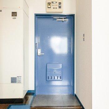 玄関扉も青。シューズラックを置くと良さそう。